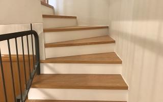 Escaleras forradas con huella de roble y contrahuella lacada blanca